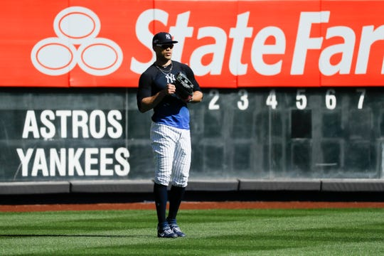 New York Yankees left fielder Giancarlo Stanton waits for balls in the outfield during batting practice before Game 3 of baseball's American League Championship Series against the Houston Astros, Tuesday, Oct. 15, 2019, in New York.