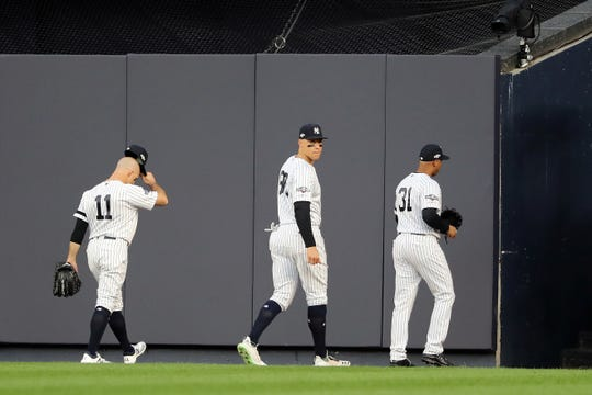 (L-R) Brett Gardner #11, Aaron Judge #99 and Aaron Hicks #31 of the New York Yankees walk off the field as the home plate umpire is replaced following the fourth inning in game three of the American League Championship Series between the Houston Astros and the New York Yankees at Yankee Stadium on October 15, 2019 in New York City.