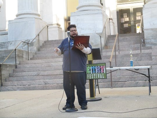 Paterson resident Rich Villar reads his work during city's recent poetry festival.