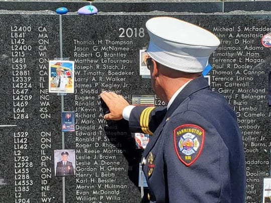 Retired Farmington Fire Department Firefighter Vince Moffit locates the name of Jacob Shadd Rohwer on the  International Association of Firefighters Fallen Fire Fighter Memorial on Sept. 21 in Colorado Springs, Colorado. Rohwer died from job-related cancer. His name was added to the memorial during a ceremony.