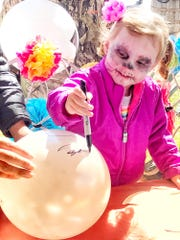 Baylee Wilson decorates a sugar-skull balloon.
