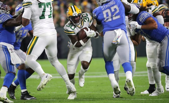 Green Bay Packers running back Jamaal Williams (30) finds a seam in the Detroit Lions defense during the second  quarter of their game Monday, October 14, 2019 at Lambeau Field in Green Bay, Wis.