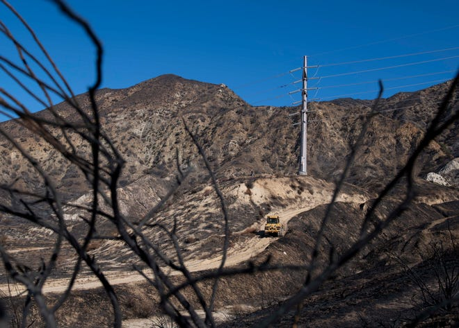 A SoCal Edison bulldozer clears the road to a transformer tower in Sylmar, Calif., on Tuesday, Oct. 15, 2019, suspected of being responsible for starting the Saddleridge fire. (AP Photo/Christian Monterrosa)
