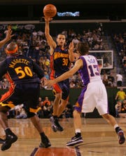 Golden State's Stephen Curry (30) tries to drop a pass over the Suns' Steve Nash during second half action in the Phoenix Suns game against the Golden State Warriors Oct.10, 2009, at the Indian Wells Tennis Garden.