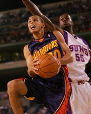 Golden State Warriors rookie Stephen Curry drives past the Phoenix Suns' Earl Clark in second half action of the Phoenix Suns game against the Warriors Saturday, Oct. 10, 2009, at the Indian Wells Tennis Garden.