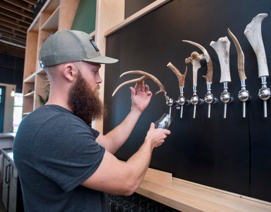 Brett Schweigert, co-founder and head brewer at Odd Colony Brewing Co., pours a glass of Holocene, a Saison pale ale, at the new brewery on Tuesday.