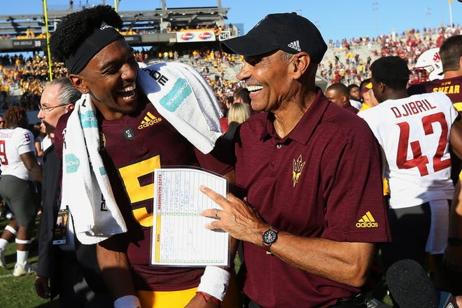 Arizona State quarterback Jayden Daniels (5) celebrates with coach Herm Edwards after beating Washington State last season.