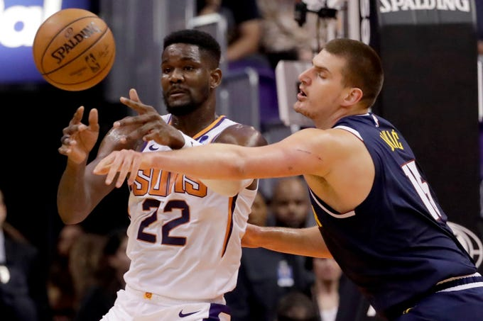 Phoenix Suns center Deandre Ayton (22) dishes off as Denver Nuggets center Nikola Jokic defends during the first half of an NBA preseason basketball game, Monday, Oct. 14, 2019, in Phoenix.