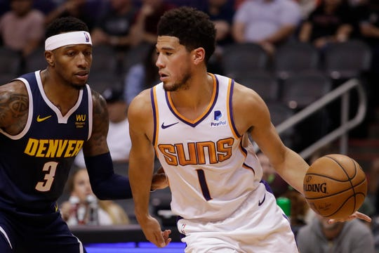 Phoenix Suns guard Devin Booker (1) moves the ball upcourt as Denver Nuggets forward Torrey Craig (3) defends during the first half of an NBA preseason basketball game, Monday, Oct. 14, 2019, in Phoenix.