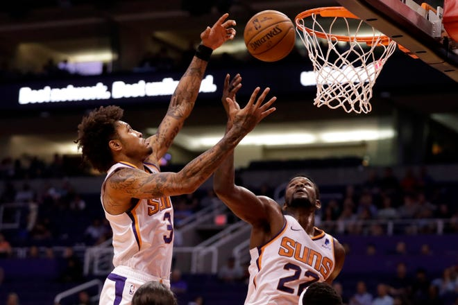 Phoenix Suns center Deandre Ayton (22) and forward Kelly Oubre Jr. (3) battle for the rebound during the first half of an NBA preseason basketball game against the Denver Nuggets, Monday, Oct. 14, 2019, in Phoenix.