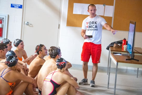 York YMCA head swim coach John Nelson frequently shows his team footage of themselves in action to help workshop their forms, October 10, 2019.