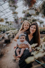The Inch family spends time at Hueter's Greenhouses, near Rocky Ridge Park, where Sarah Inch (center) owns Gray Apple Garden House. Behind her is Jozlyn Inch, and she's holding River, now 10 months old. Photo taken by Cambria Cross.