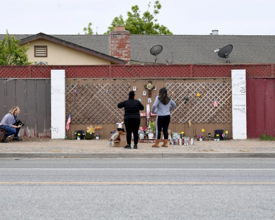 "Reporter Kate Cimini (left) with The Salinas Californian takes photos of the family of Enrique ""Kiki"" Sosa at this memorial on Russell Road in fall 2019."