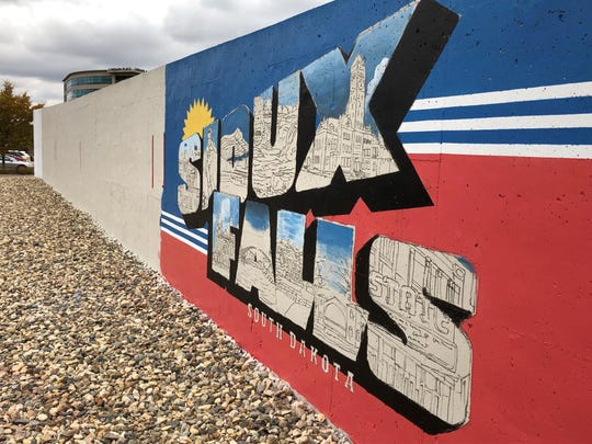 "Zach DeBoer is one of five artists who is starting a mural project on a concrete wall near the Raven building in downtown Sioux Falls. DeBoer's portion is a take off the iconic ""Greetings From Sioux Falls"" postcard."