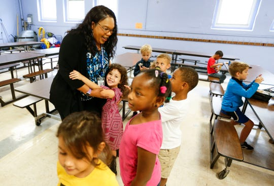 Boyd Elementary School Principal Angela Holloway Payne receives a hug from student Mackenzie Gonzales during lunch.