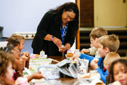 Boyd Elementary Principal Angela Holloway Payne stops at a table full of students during lunch to help one child.