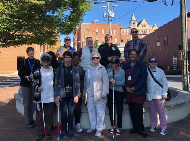 Participants in the second annual White Cane Day walk posed for a photo near the Wharf parking lot in Staunton.