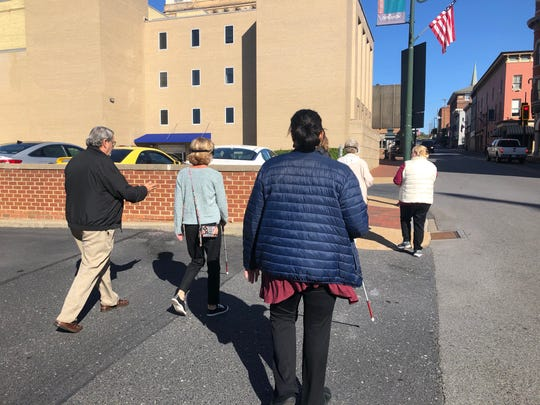 Some participants were using a cane for the first time, some were frequent cane users and some helped people navigate. This photo shows the group walking down South Augusta Street.