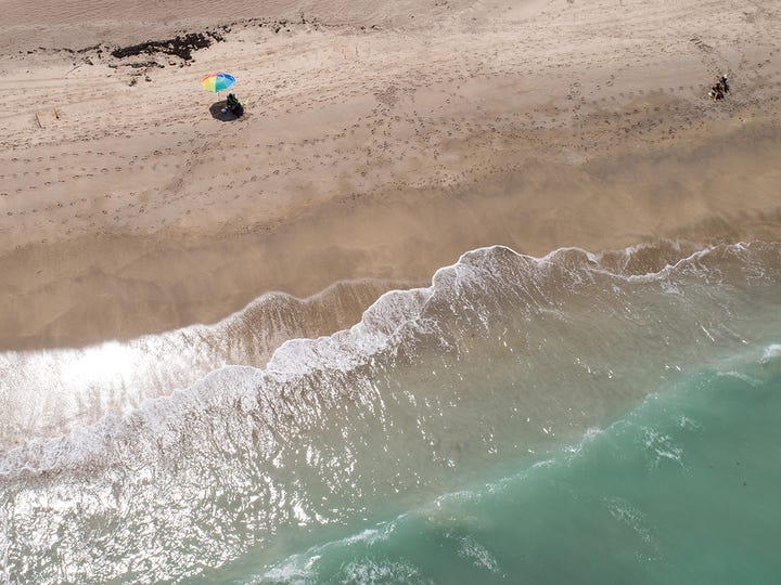 Beachgoers relax at Jensen Beach, seen in a drone aerial Wednesday, Aug. 28, 2019, days before Hurricane Dorian.