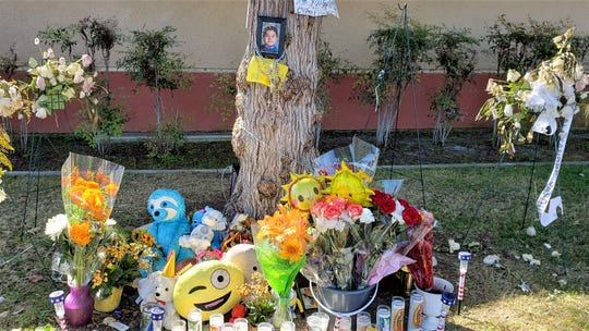 Flowers, candles, toys and other tributes adorn a memorial for Alexander Vasquez, 8, who died after he was hit by a van while crossing Cooper Road on the way to school on Sept. 30.