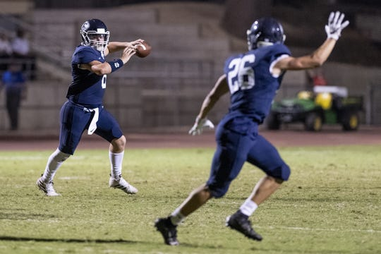 Redwood quarterback Ryan Rios passes to running back Caden Shafer against Porterville in a non-league high school football game on Friday, September 27, 2019.