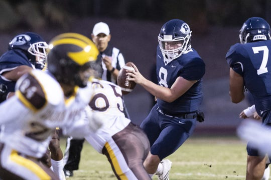 Redwood quarterback Ryan Rios escapes pressure against Golden West in a West Yosemite League high school football game on Friday, October 11, 2019.