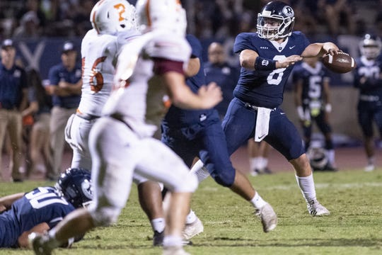 Redwood quarterback Ryan Rios drops back to pass against Porterville in a non-league high school football game on Friday, September 27, 2019.