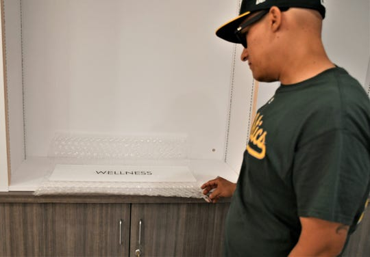 "Token Farms Manager Anthony Rosales shows a ""wellness"" category sign to be hung in the showroom of the soon-to-be open Farmersville dispensary."