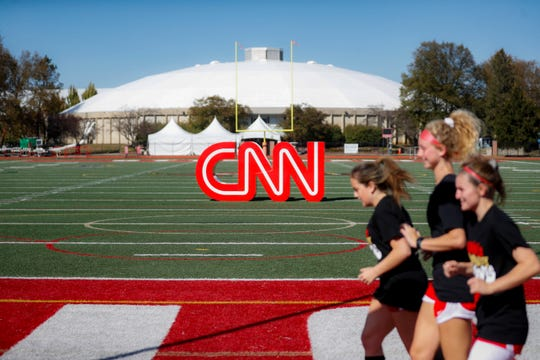 Student athletes pass a CNN sign on an athletic field outside the Clements Recreation Center where the CNN/New York Times will host the Democratic presidential primary debate at Otterbein University, Monday, Oct. 14, 2019, in Westerville, Ohio.
