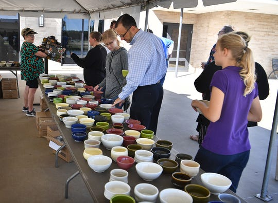 Patrons of the 8th Annual Empty Bowls Wichita Falls event pick out their bowls Tuesday at the Wichita Falls Museum of Art at Midwestern State University. The event is a fundraiser for the Wichita Falls Area Food Bank.
