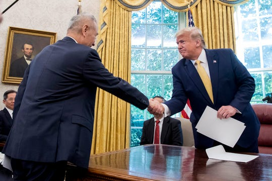 FILE - In this Oct. 11, 2019, file photo, U.S. President Donald Trump, right, shakes hands with Chinese Vice Premier Liu He after being given a letter in the Oval Office of the White House in Washington. China's trade with the United States fell by double digits again in September amid a tariff war that threatens to tip the global economy into recession.