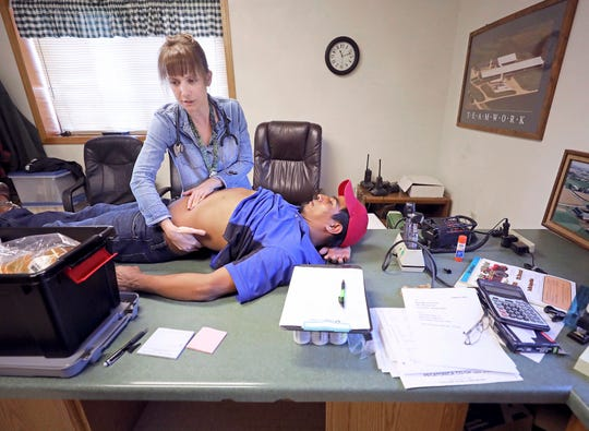 Dr. Emily Jewell, who volunteers with the Community Connections Free Clinic in Dodgeville, Wis., examines the abdomen of Orvilio Lopez, a worker at Cottonwood Dairy near Wiota, Wis. on Sept. 23, 2019. The free clinic started bringing staff and supplies on a bus to farms last fall to provide care for workers without insurance.