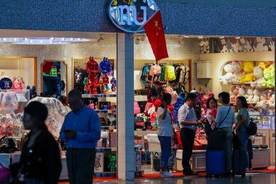 Passengers shop at the Shanghai Disney flagship store at the Hongqiao Railway Station in Shanghai, China, Monday, Oct. 14, 2019. China's trade with the United States fell by double digits again in September amid a tariff war that threatens to tip the global economy into recession.