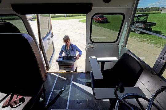 Dr. Emily Jewell, a volunteer with the Community Connections Free Clinic in Dodgeville, Wis., unloads medical supplies for health assessments of workers at Cottonwood Dairy in Wiota, Wis. on Sept. 23, 2019. The free clinic started bringing staff and supplies on a bus to farms last fall to provide care for workers without insurance.