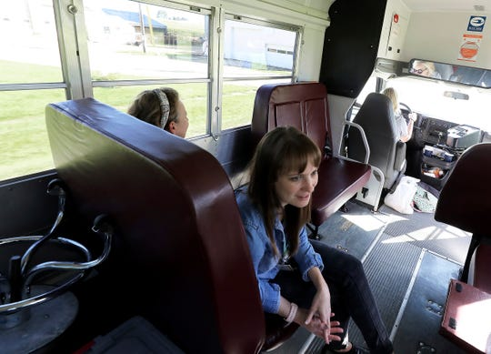 Dr. Emily Jewell, center, a volunteer with Community Connections Free Clinic in Dodgeville, Wis., rides a bus with her mother, Marcia Jewell, a volunteer nurse with the clinic, left, and Rebecca Steffes, the clinic's nurse manager, during a trip to Cottonwood Dairy in Wiota, Wis. on Sept. 23, 2019. The free clinic started bringing staff and supplies on a bus to farms last fall to provide care for workers without insurance.