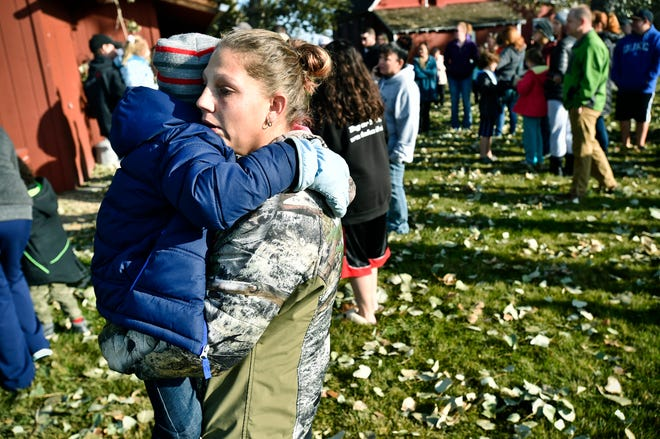 Marnie Wedgwood hugs her son on the Rossiter Elementary school playground Tuesday, Oct. 15, 2019, in Helena, Mont.