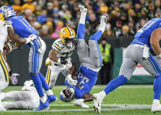 Detroit Lions running back Kerryon Johnson  is upended on a tackle by the Green Bay Packers in the first quarter at Lambeau Field in  Green Bay, Wis.