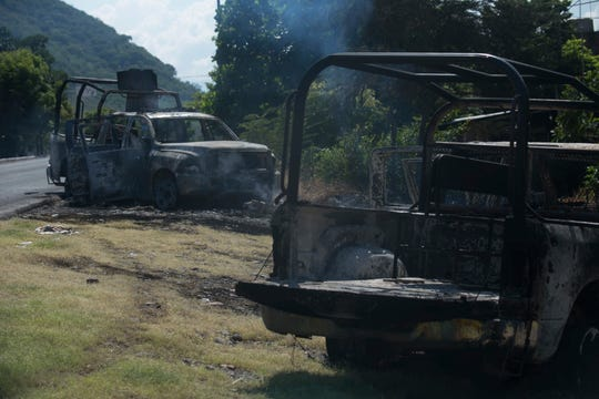 Charred trucks that belong to the Michoacan state police stand on the roadside after they were attacked in El Aguaje, Mexico, Monday, Oct. 14, 2019. At least 13 police officers were killed and nine others injured in the ambush.
