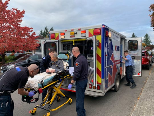 Vancouver, Washington EMS loads Bill Davis, 90, into an ambulance Oct. 12 after city council candidate David Regan gave him first aid. Regan was canvassing for votes at Davis's home when he fell and hit his head.