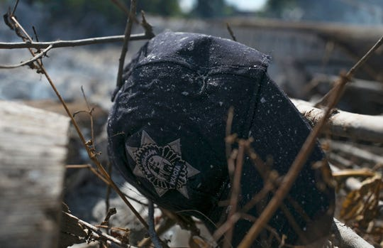 The cap of a Michoacan state police officer lies in the brush where charred police trucks stand on the roadside after its police officer occupants were attacked in El Aguaje, Mexico, Monday, Oct. 14, 2019.
