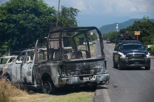 A charred truck that belongs to Michoacan state police sits on the side of the road after it was burned during an attack, as state police drive past in El Aguaje, Mexico, Monday, Oct. 14, 2019.