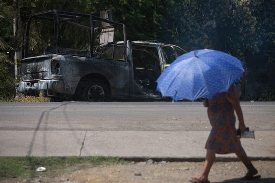 A pedestrian walks past a charred truck that belongs to Michoacan state police, after it was burned during an attack in El Aguaje, Mexico, Monday, Oct. 14, 2019.