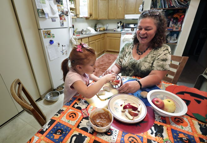 Shawn Hansen and her daughter Chloe, 4, make a caramel apple snack at their home in Menasha.