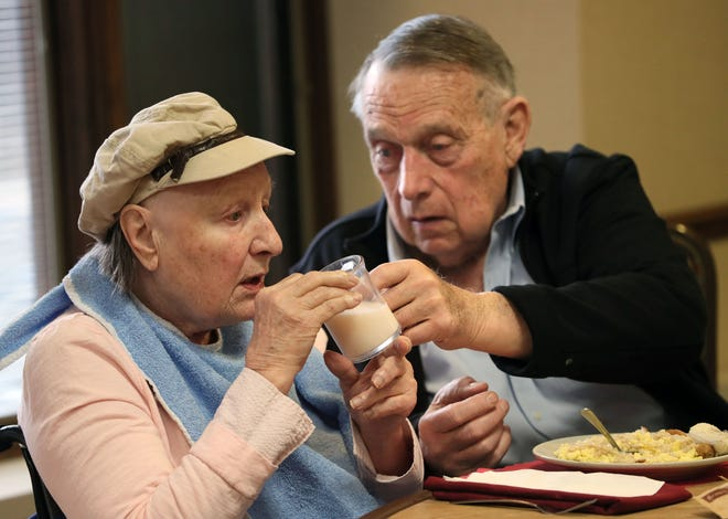 Former Wisconsin Gov. Marty Schreiber helps his wife, Elaine, with a glass of milk during breakfast at Lutheran Home in Wauwatosa in April. She has Alzheimer's disease.