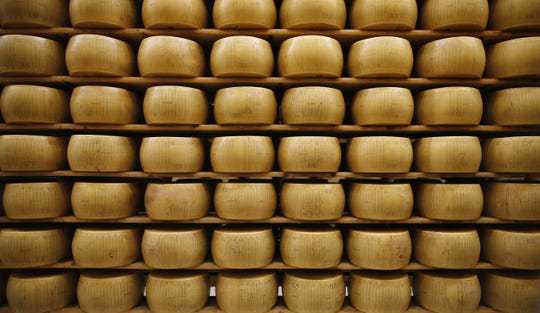 In this Oct. 8, 2019, file photo, Parmigiano Reggiano Parmesan cheese wheels are stored in Noceto, near Parma, Italy. The tariffs the Trump administration is about to impose on wine, liquor and cheese from Europe couldn't come at a worse time for small retailers.