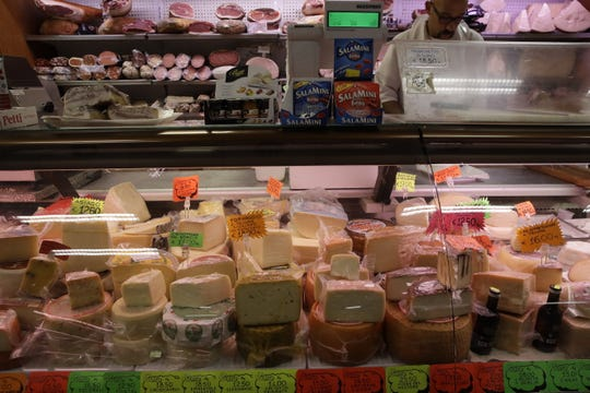 In this Oct. 3, 2019, file photo, blocks of Italian cheese are on sale in a deli in Rome. The tariffs the Trump administration is about to impose on wine, liquor and cheese from Europe couldn't come at a worse time for small retailers.