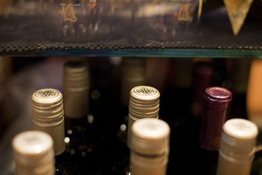 This Dec. 25, 2018, photo shows wine bottles at the bar at a bowling alley in Eagle, Colo. No one expects consumers to completely abandon Bordeaux wine from France, Scotch whisky or cheeses like Stilton, Roquefort when the tariffs take effect Friday, but retailers as well as their importers and distributors are aware that buying habits may change if shoppers fear they're now paying 25% more for their favorite drinks and delicacies.