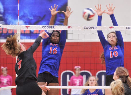 Cooper's Dazz Larkins (16) and Brianna Garcia (10) defend at the net as Wichita Falls High's Ashlyn Lewis hit the ball. Cooper beat the Lady Coyotes 25-14, 22-25, 25-12, 25-10 in a District 4-5A volleyball match Tuesday, Oct. 15, 2019, at Cougar Gym.