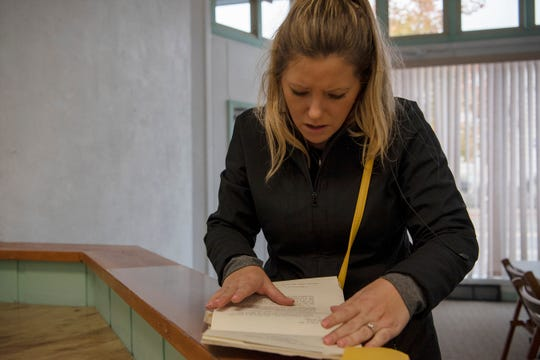 Sarah Versical flips through titles, deeds and other documents of 70 E. Michigan Ave. Wednesday morning on Oct. 16, 2019 in downtown Battle Creek, Mich. Sarah and her husband Jeff purchased the historical building in May to renovate into affordable housing, an issue of accessibility realized during their search to move downtown and into the heart of a city they love.