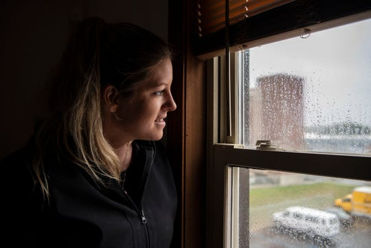 Sarah Versical peers out a window of 70 E. Michigan Ave. Wednesday morning on Oct. 16, 2019 in downtown Battle Creek, Mich. Sarah and her husband Jeff purchased the historical building in May to renovate into affordable housing, an issue of accessibility realized during their search to move downtown and into the heart of a city they love.